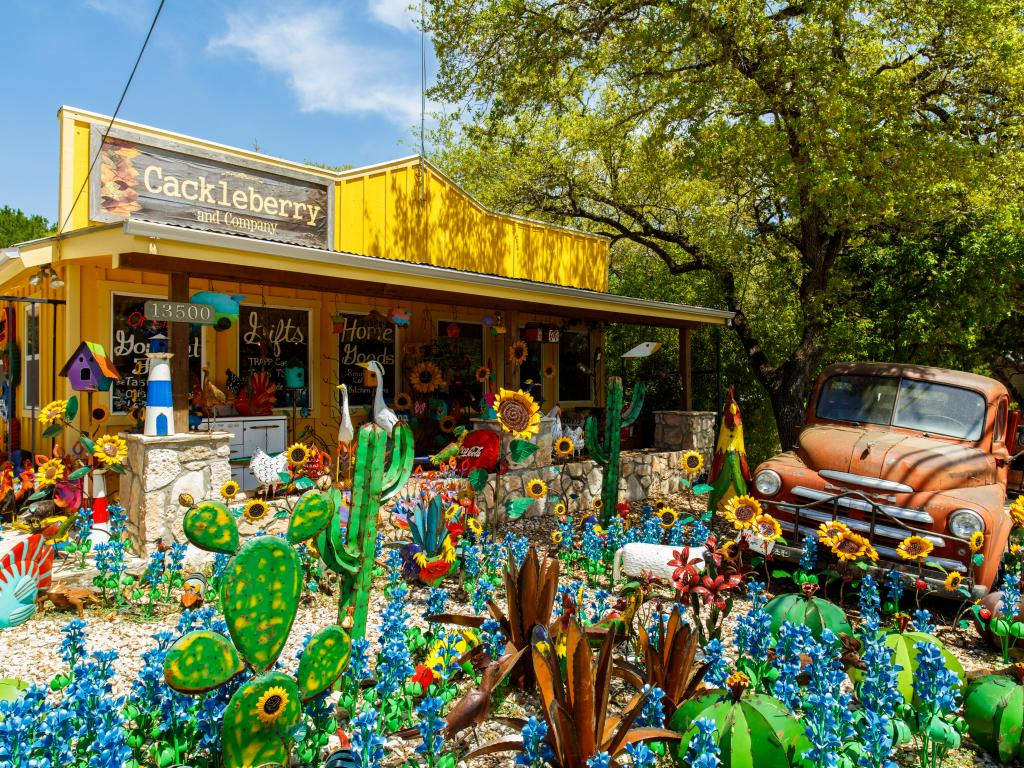 Colorful shop with art and artificial plants and an old pickup truck in Wimberley, Texas.