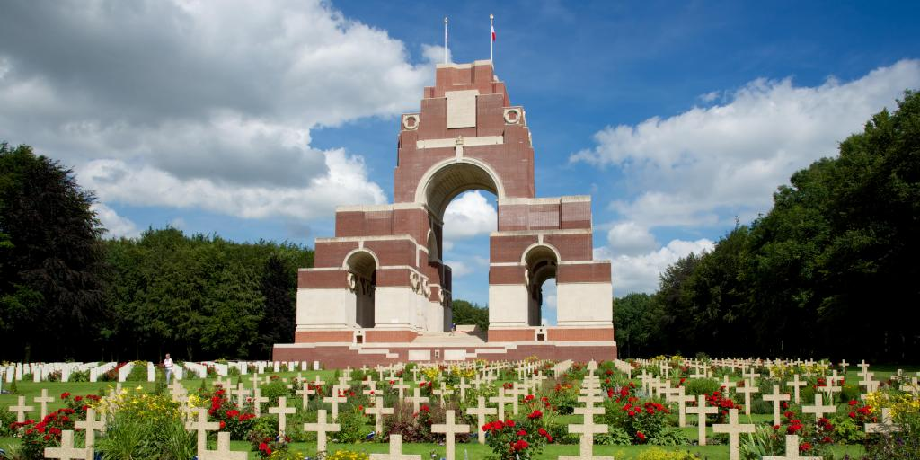 The brickwork arches of the Thiepval Memorial, France, with rows of crosses and red flowers in front