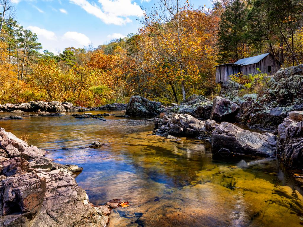 An abandoned wooden mill on the rocks next to a river in the Mark Twain National Forest in the fall.