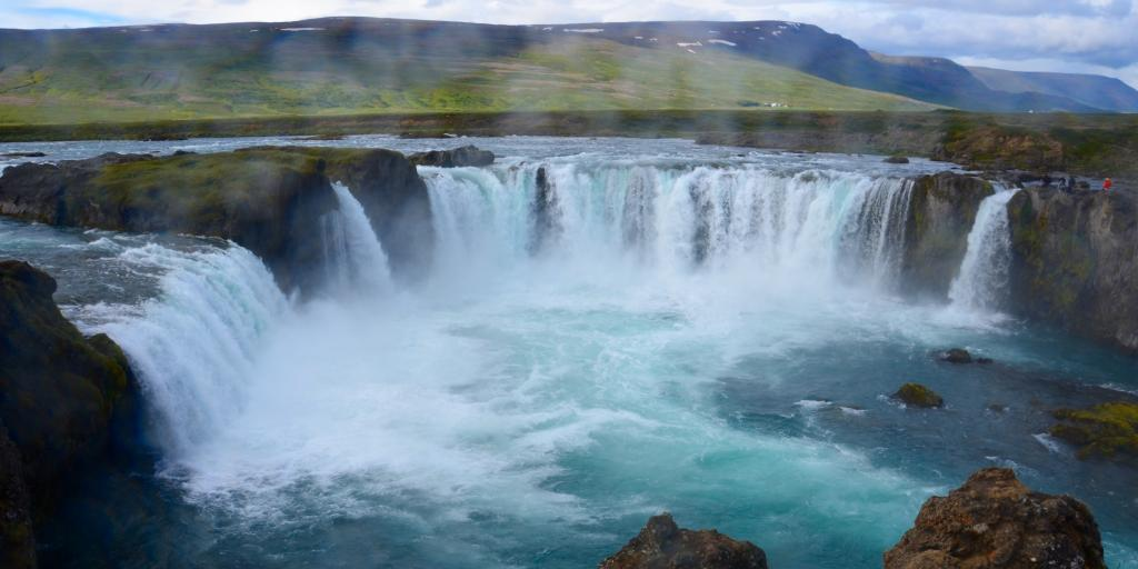Ice blue water cascades over the edge of Godafoss waterfall