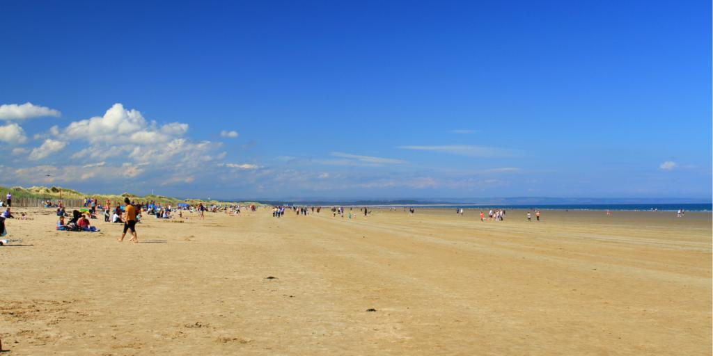 People enjoying St Andrews beach on a sunny day