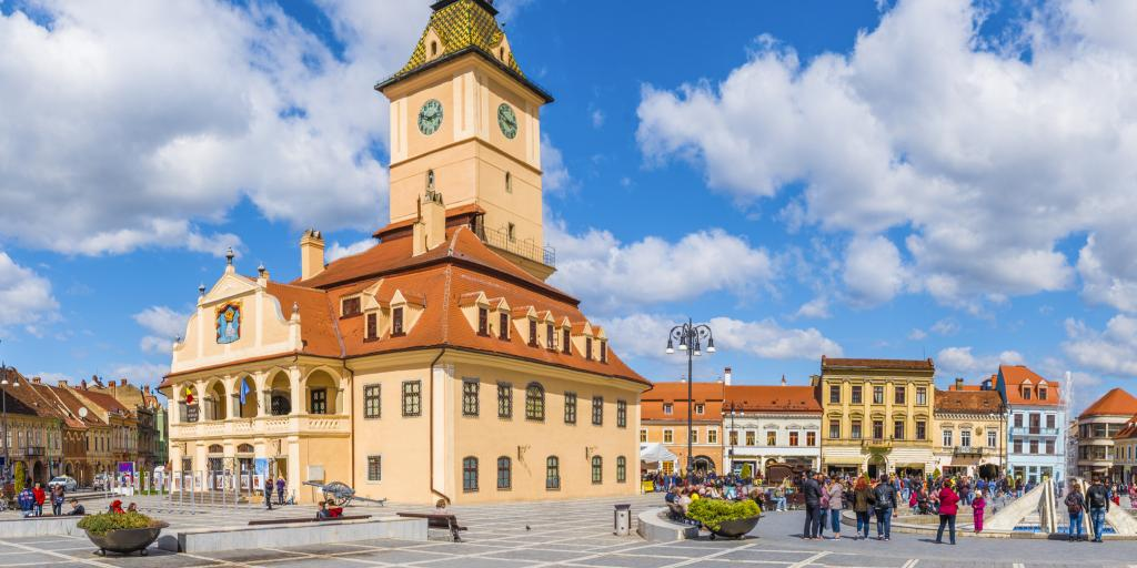 A view of the former council house surrounded by colourful buildings and people exploring in Council Square, Brasov