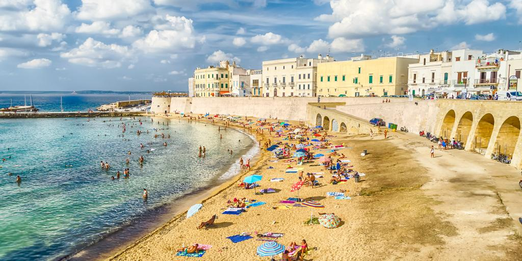 People relaxing on Purity Beach with the town walls behind in Galipolli, Puglia