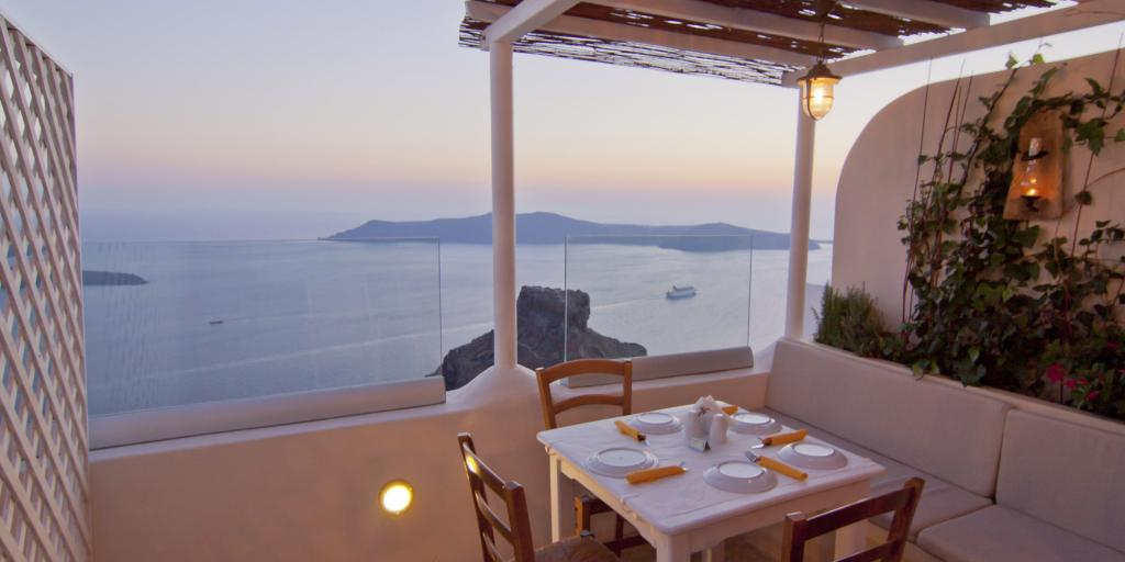 A table set for four with views of the caldera in Santorini at dusk