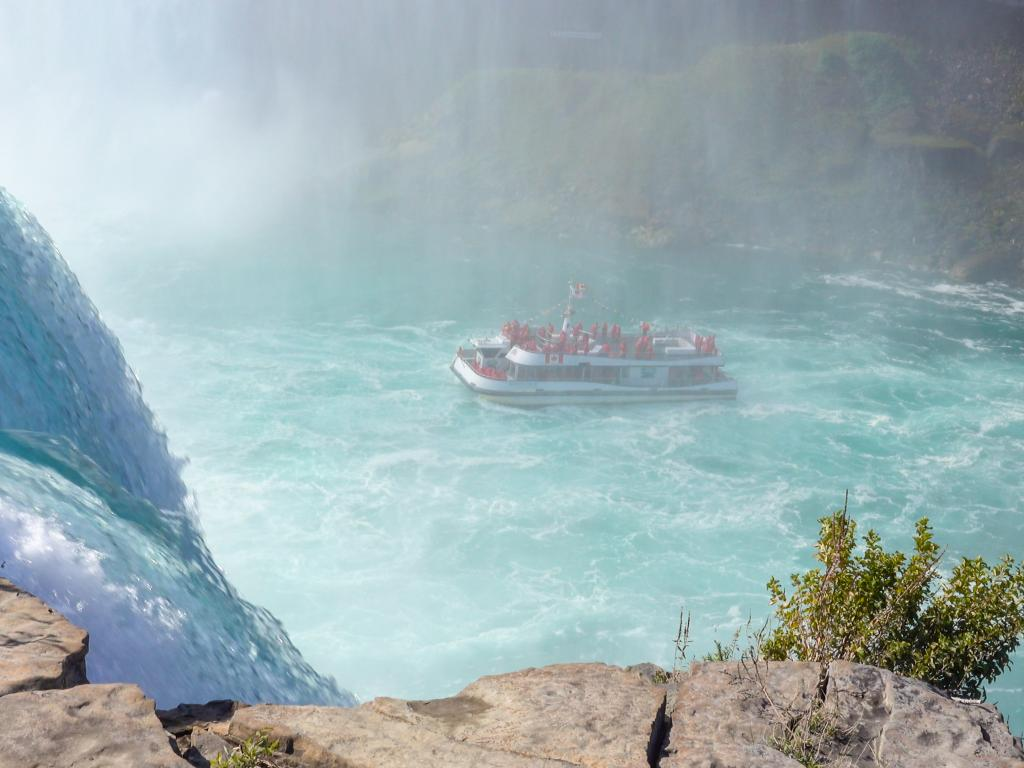 An amazing sight of a tour boat cruise with tourists enjoying the mists and witnessing the raging waterfall of Niagara Falls