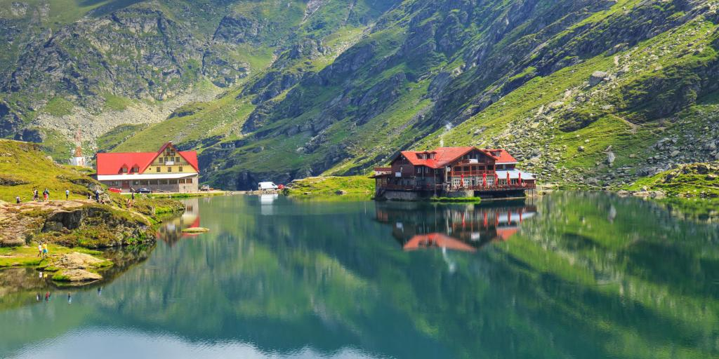 Chalets and mountains reflected on Balea Lake in Romania