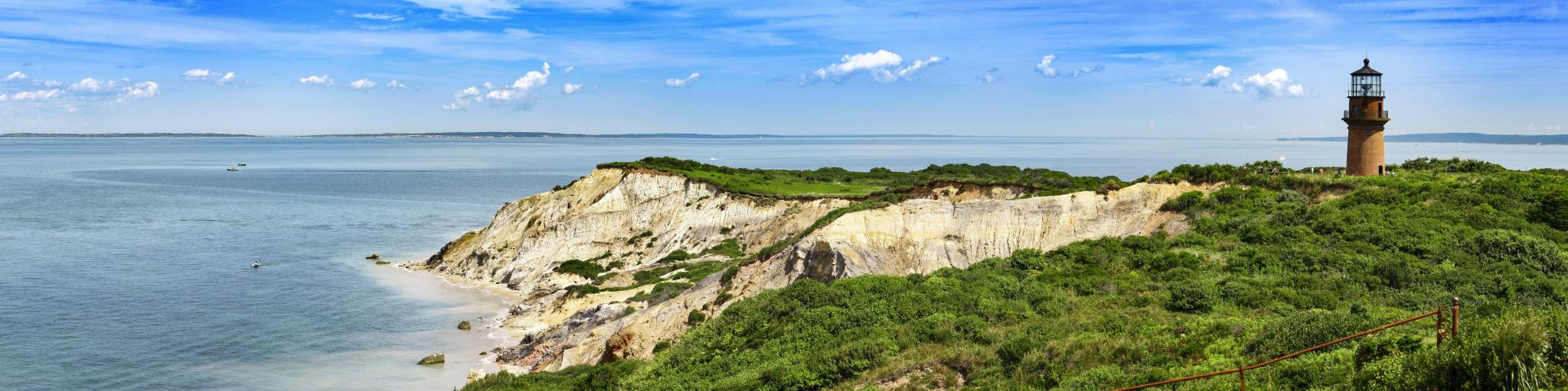 A panoramic view of the Coastal Lighthouse on a green grassy cliff with a mirroring sky and sea of blue with fluffy cotton-like clouds in Aquinnah, Martha's Vineyard