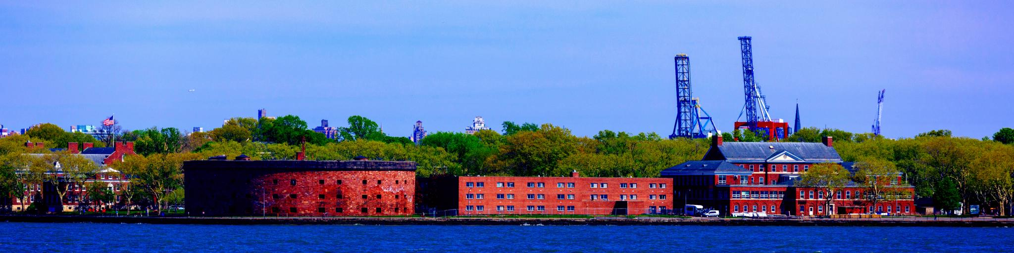 A worm's eye view of Castle Williams of General Island from New York Harbor with trees green trees and tower in the back on a sunny day