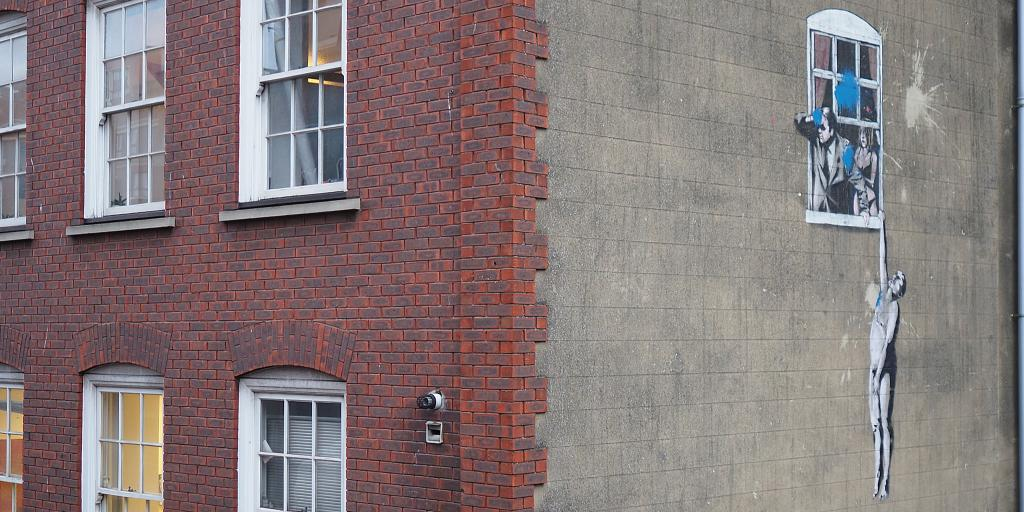 A famous Banksy graffiti on the side of a building in Bristol