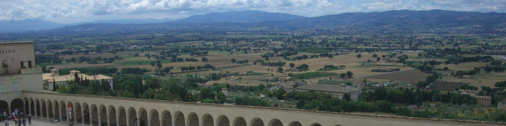 The arches of Basilica of Saint Francis of Assisi with the Italian town of Assisi in the background