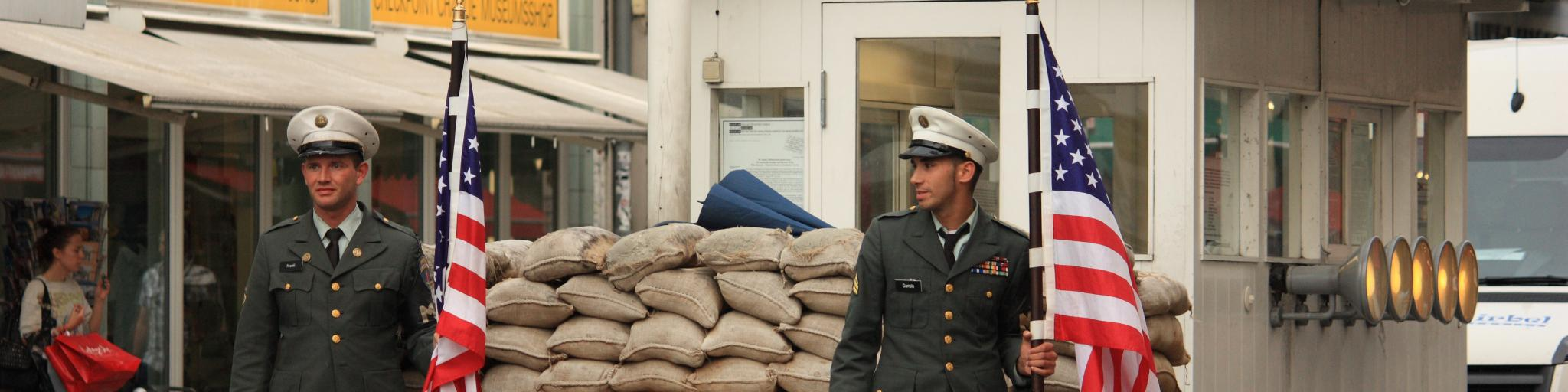 Two guards hold American flags at Checkpoint Charlie in Berlin