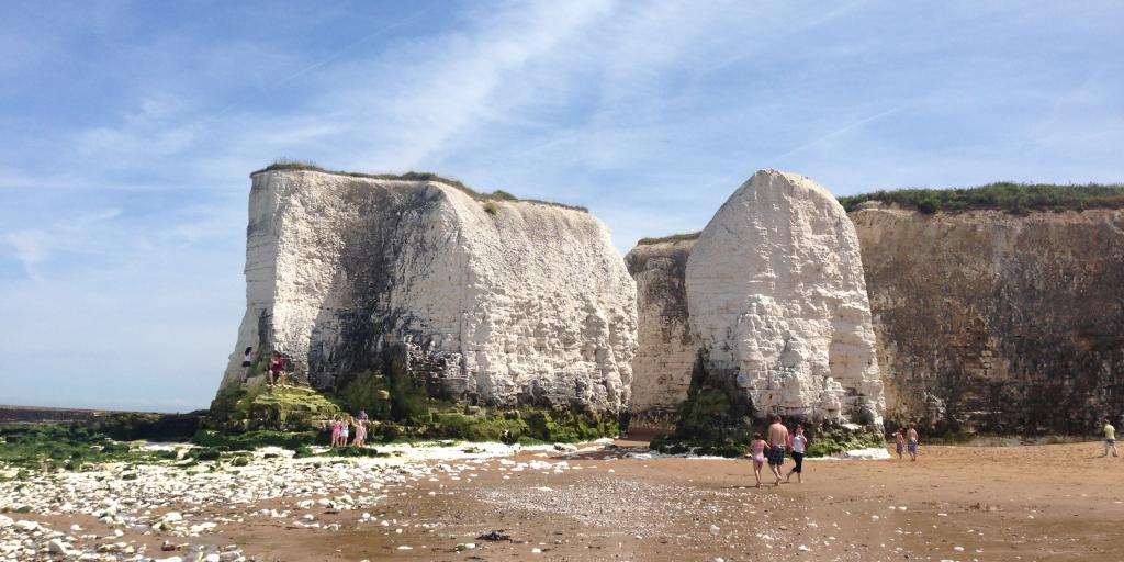 White cliffs jut out from the sand as beachgoers explore Botany Bay