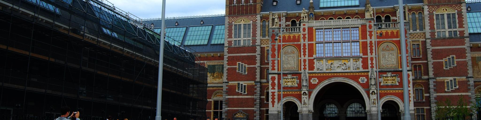 Tourists come in and out of the Rijksmuseum,  a grand red building in Amsterdam