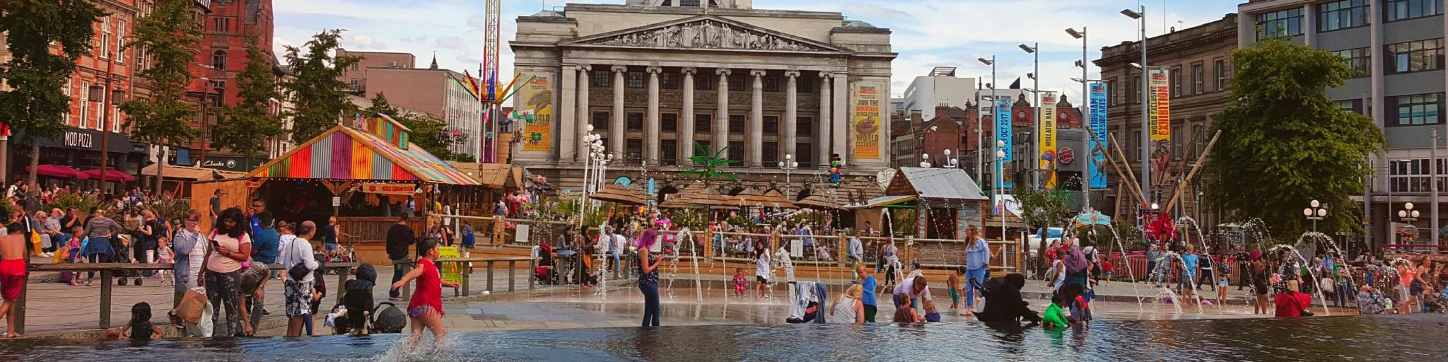 People play in the fountain in front of Nottingham Town Hall in Market Square