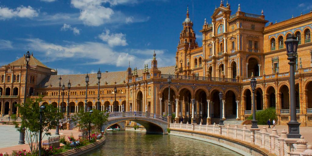A bridge crosses the most in front of Plaza de Espana in Seville, Spain