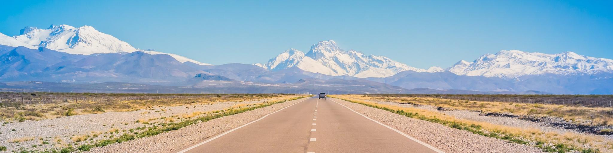 A car on an empty road in Mendoza, Argentina, with mountains in the background