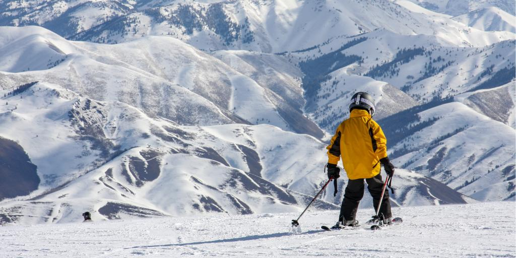 Skier in a yellow jacket going down a mountain in Sun Valley, Idaho