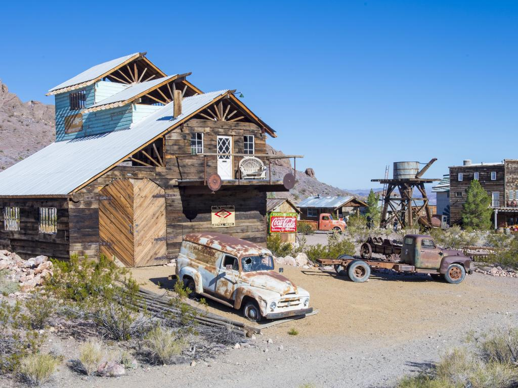 The abandoned Nelson Ghost Town with rusty old cars and derelict buildings.