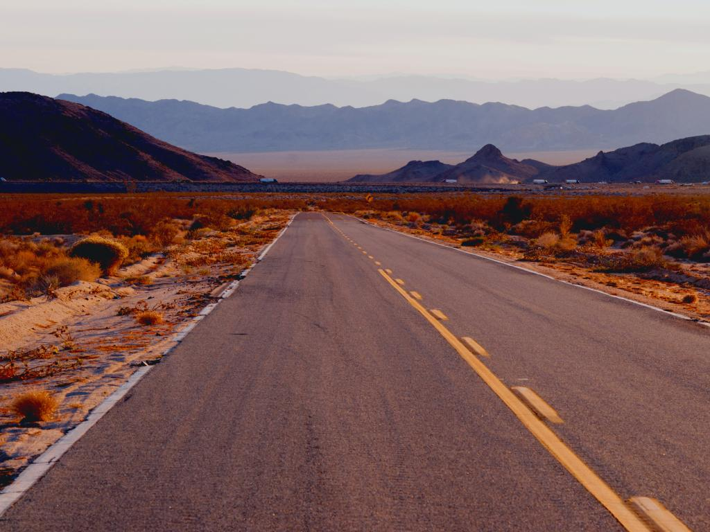 An empty Interstate 40 along Needles Freeway in Mojave National Preserve with a view of mountains on a hazy afternoon.