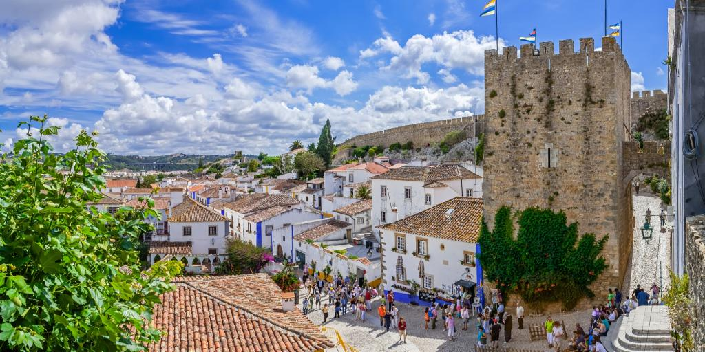 People sit on the steps in front of Obidos Castle in Portugal  on a sunny day