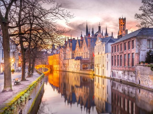 A winter sunset over an arched bridge in Bruges, Belguim,