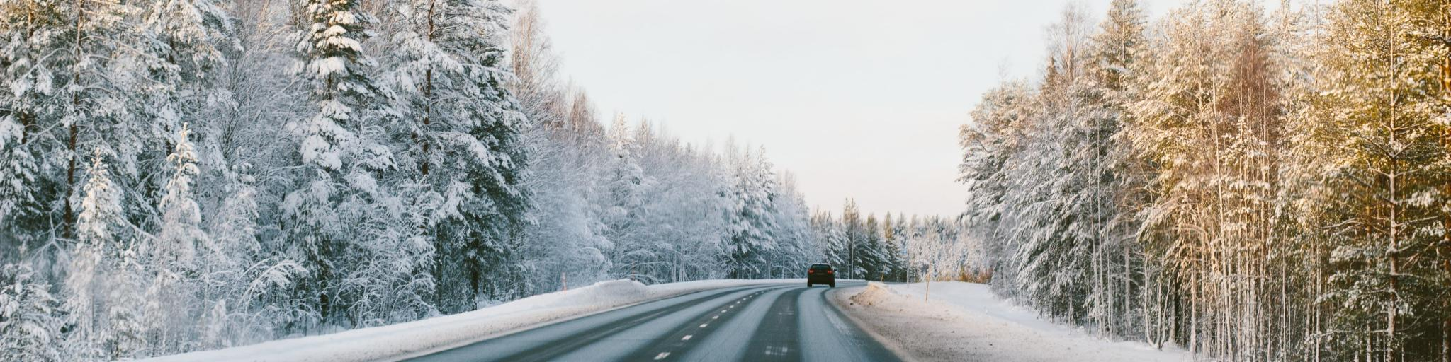 A car driving down the right side of a road surrounded by snowy trees