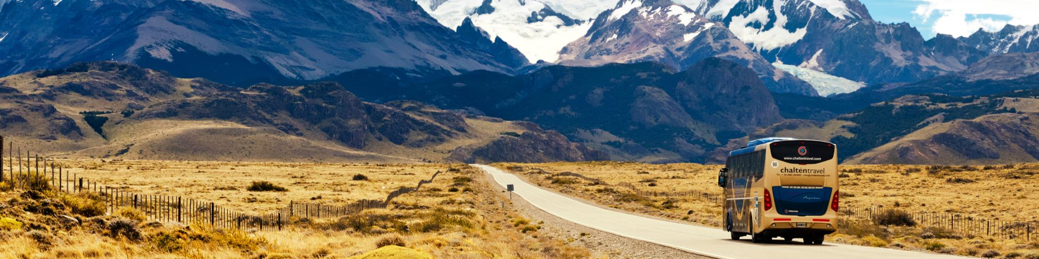 A bus driving along a deserted road towards some snow-capped mountains in Argentina