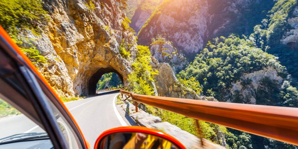 Edge of a red car going through a mountain tunnel on a sunny day