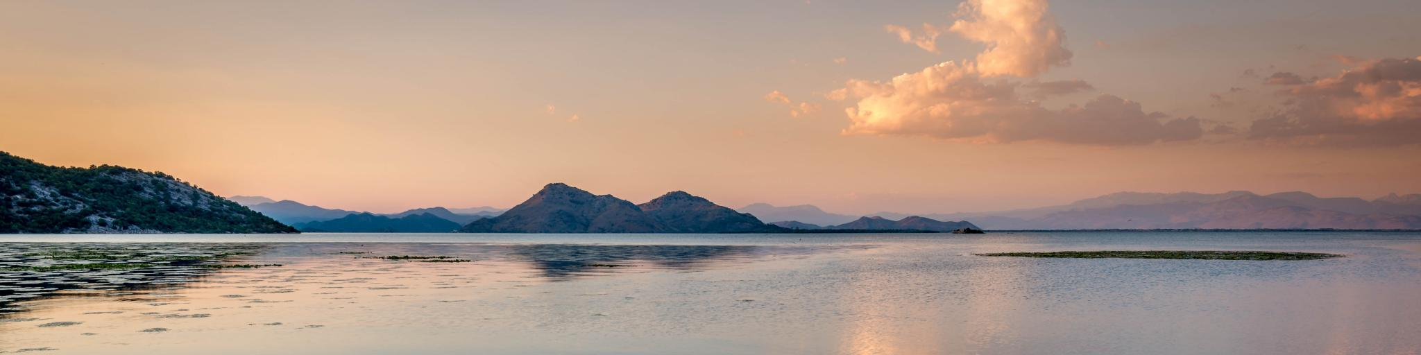 Sunset-tinged clouds reflect on the still water of Skadar Lake