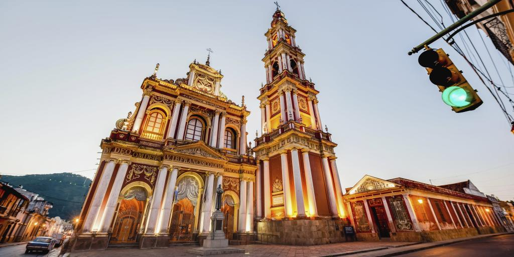 The red and gold exterior of the Basilica and Convent of San Francisco in Salta, Argentina, with a car and traffic light also in shot