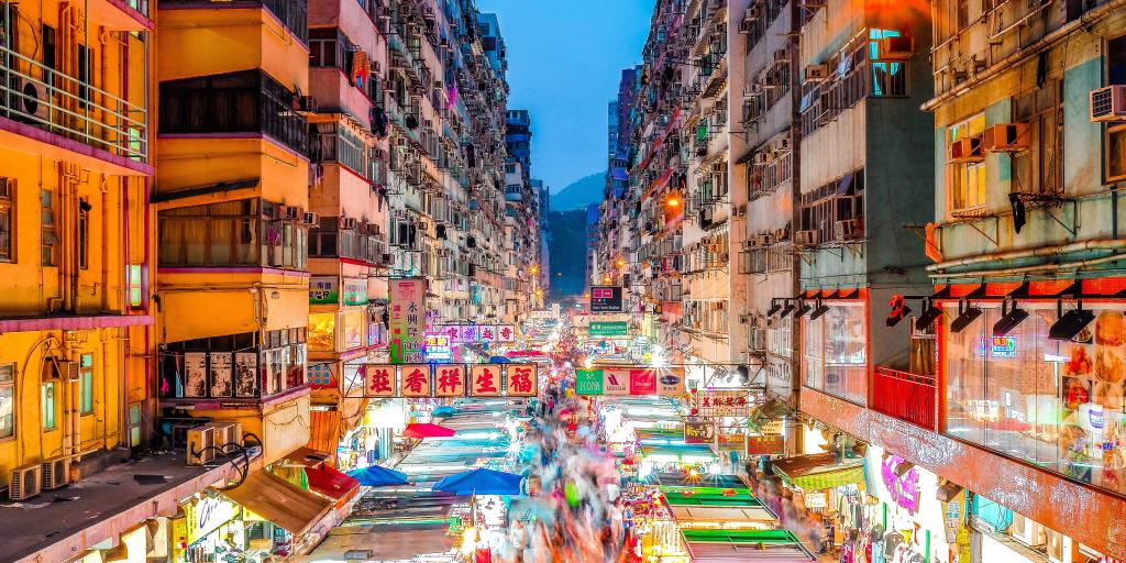 A view over the bright lights of the stalls of Mong Kok markets, Hong Kong, between the rows of high rise buildings
