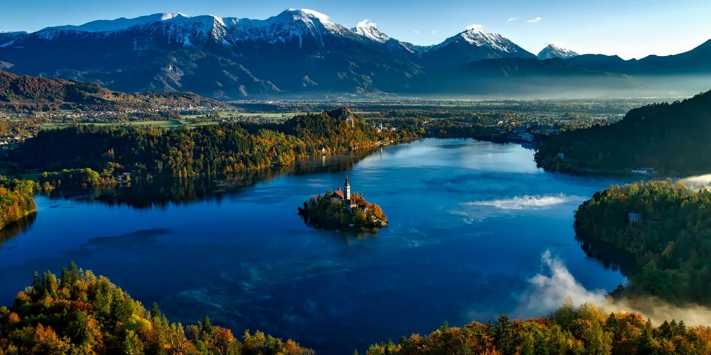 Bled Castle in the middle of Lake Bled is surrounded by colourful autumn leaves