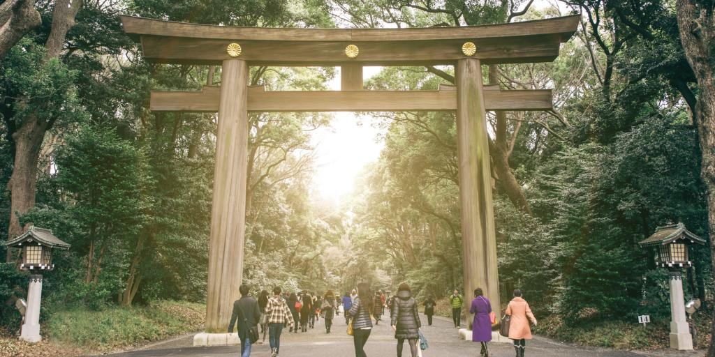 Visitors walking through the torii gate of the Meiji Shrine, Tokyo