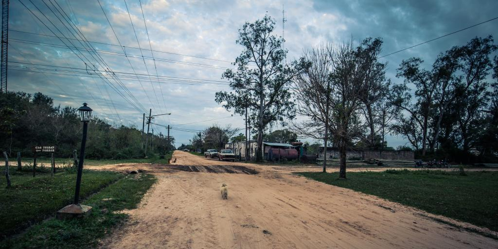 A muddy cross roads with a streetlight to one side in the town of Colonia Carlos Pellegrini, Argentina