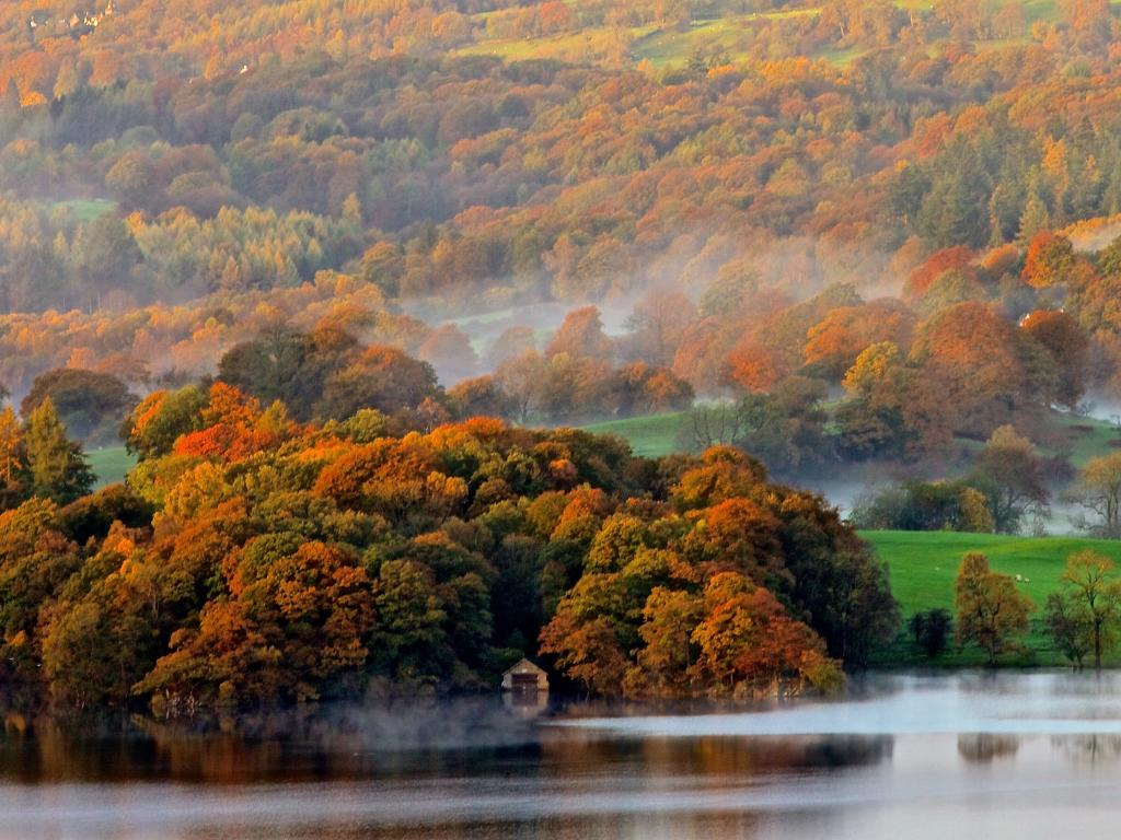 A morning mist rolls over the colourful trees and glittering Lake Windermere in the Lake District