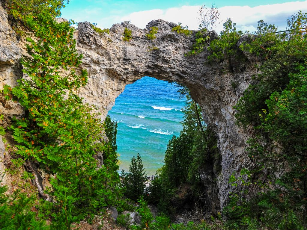 A picturesque view of Lake Huron through a natural Arch Rock with wedges growing in the walls on Mackinac Island Michigan in a sunny morning