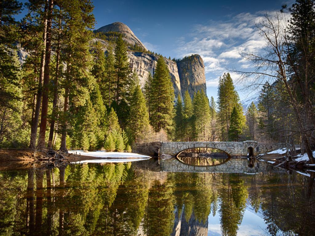 Stoneman bridge over the perfectly still Merced River in Yosemite National Park, California
