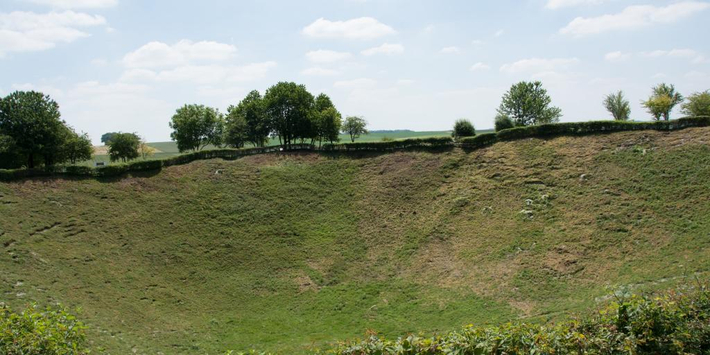 A section of the Lochnagar Crater, France, now covered in grass, with a hedge in front and trees behind