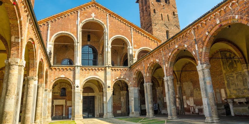 Basilica of Sant'Ambrogio church in Milan, Italy, with bell towers, courtyard, arches, and blue sky background