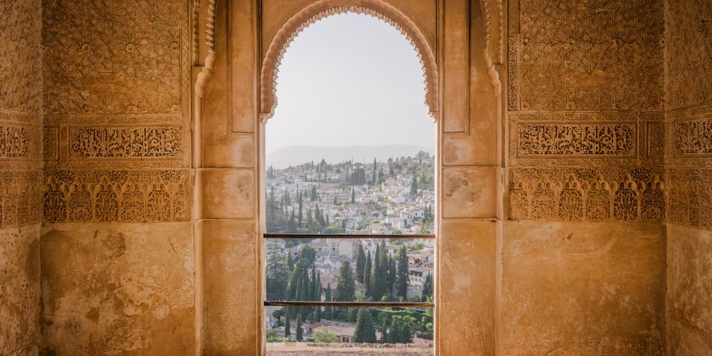 The rooftops and trees of Granada as seen through a Moorish door in the Alhambra fortress