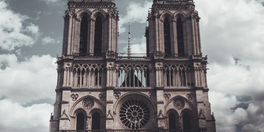 The Notre Dame de Paris towers over the city on a cloudy day
