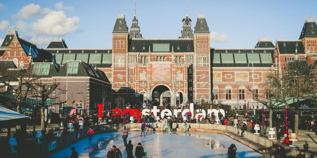 Shot of the Rijksmuseum and I Amsterdam sign with people ice skating