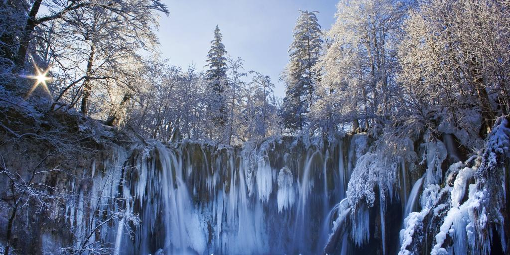 A frozen waterfall in Plitvice National Park surrounded by snow coated trees