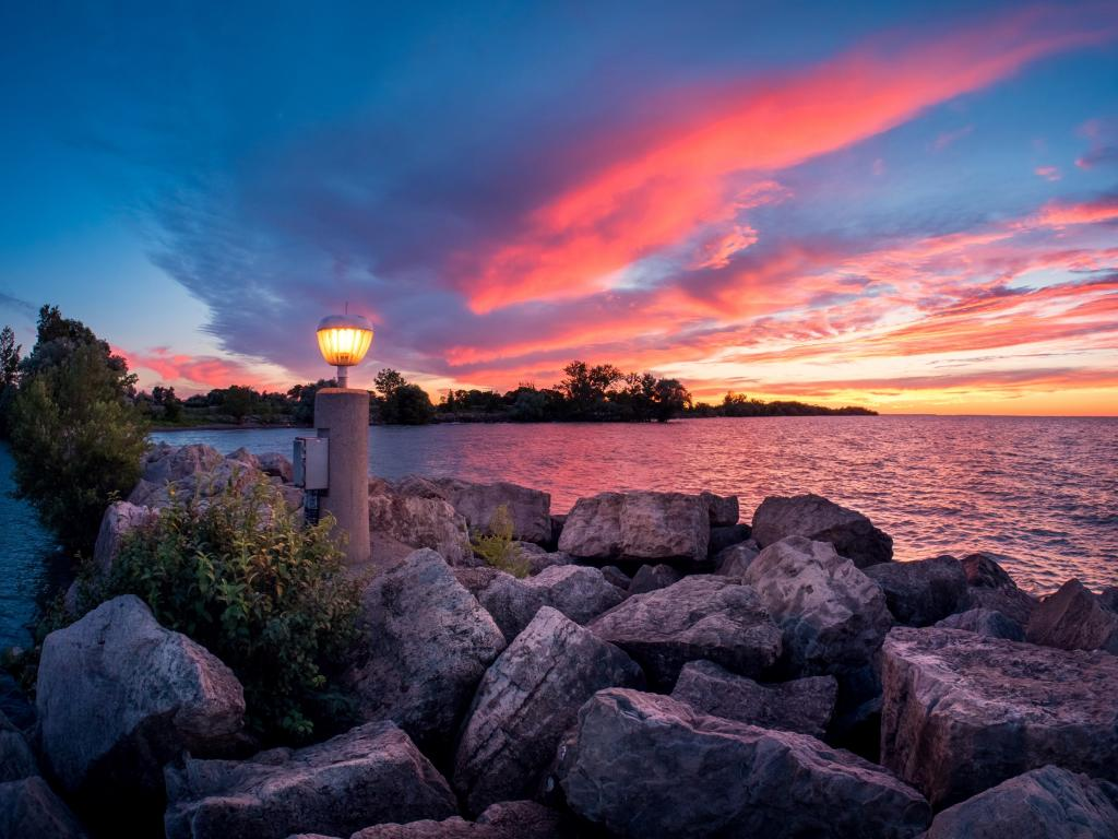 Bright sky at sunset and lamp on the shore of Lake Ontario in Canada