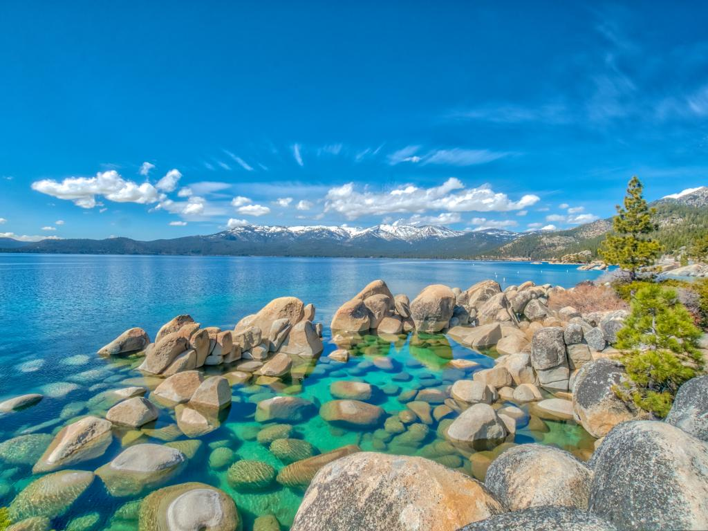 Rocks and pristine water of Lake Tahoe with snow-capped mountains in the background.