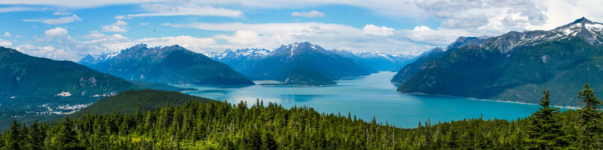Haines, Alaska surrounded by snow-capped mountains and ocean inlets on a summer day.