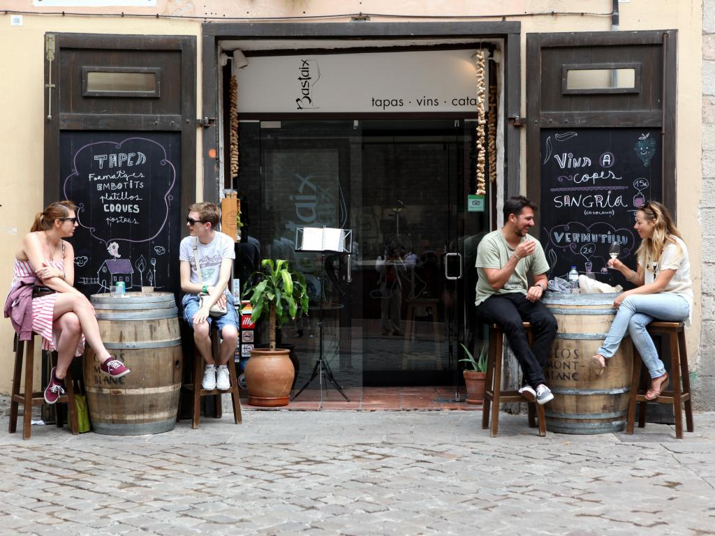 People eating outside at a Barcelona cafe on a central street