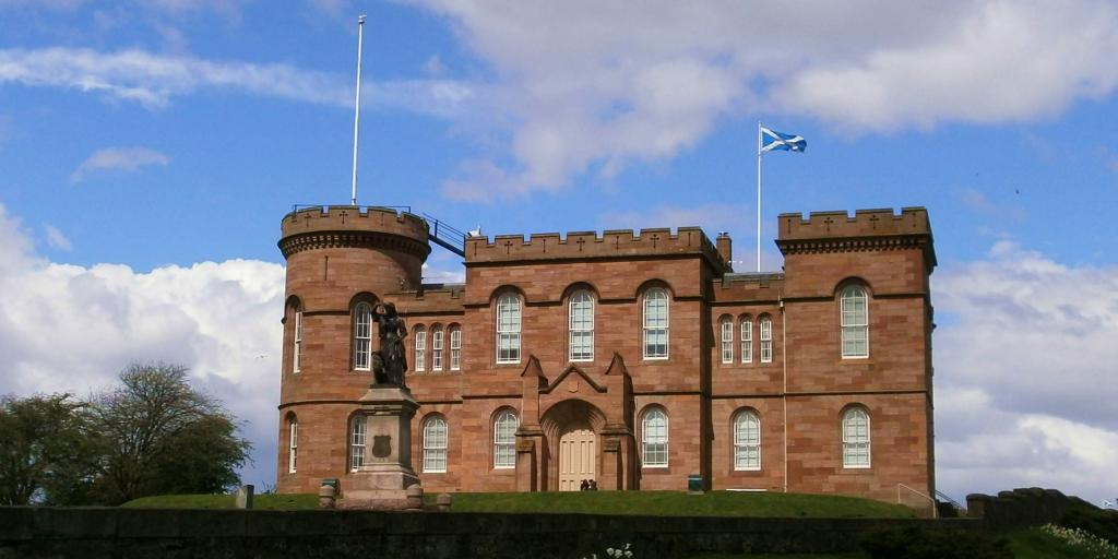 The front of Inverness Castle with a circular battlement on the left side and a Scottish flag flying above it