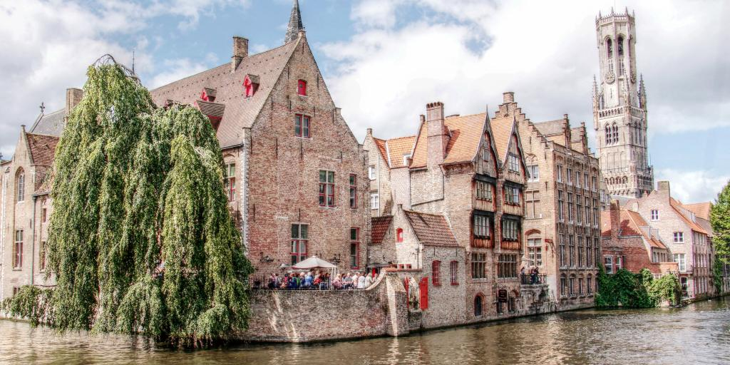 People stand under an umbrella at a restaurant on the river in Bruges, Belgium, with the belfry in the distance