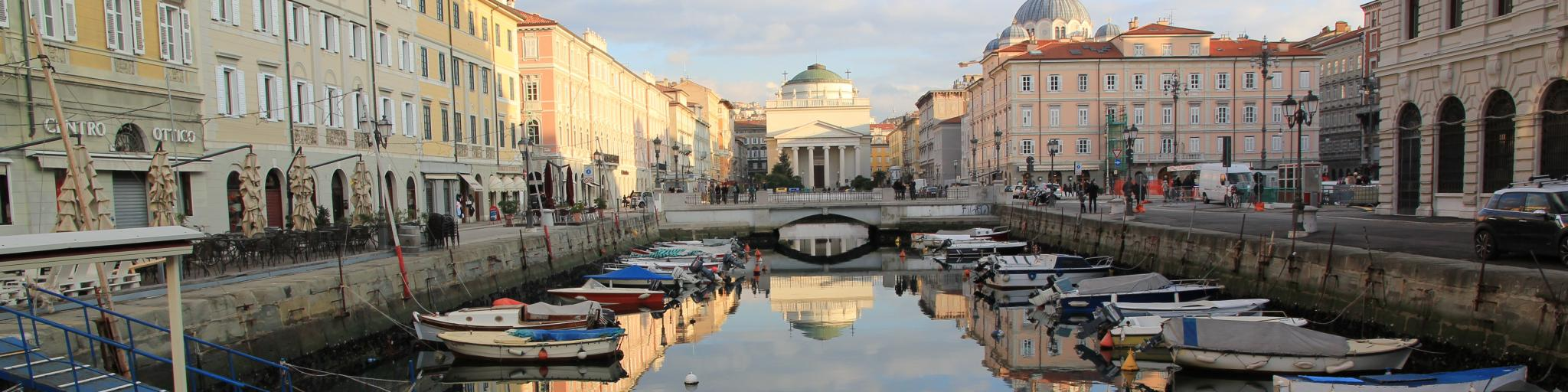 Clouds reflect on a canal in the middle of Trieste, Italy